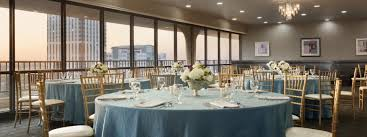 round tables with teal linens and flower displays in event room
