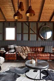 a chic industrial man space with brown leather sofas, pendant lamps and a  metal coffee