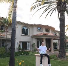 faze rug car. faze rug sitting on a concrete pillar, behind him is two storied house faze car