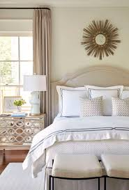 Classic bedroom style with neutral upholstered headboard, mirrored bedside  table and gold sunburst mirror above