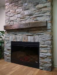 transitional stone veneer fireplace featuring reclaimed wood mantel shelf