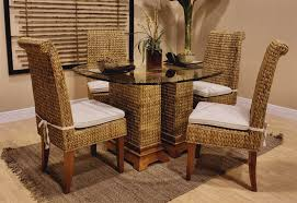 round glass high table and rattan legs decor vase flower on top with rattan chair with high wingback plus white fabric cover stand on gray rug on wooden