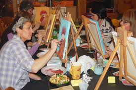 linda varney concentrates on her rooster during a paint and sip event at lil g s in ellsworth across the table instructor twilla manheim offers ashlee
