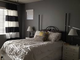 bedroom grey wall theme and black white striped window curtains on the hook connected by