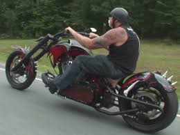 a photograph featuring paul teutul from oc choppers riding an ugly custom harley davidson motorcycle while