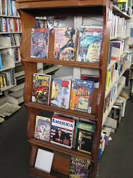 Photo of bookshelf containing various colorful comic books and hardcovers.