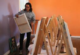 alejandro castanon removes a painting wednesday in preparation of the upcoming art show at vino dipinte art gallery 602 orient st the opening