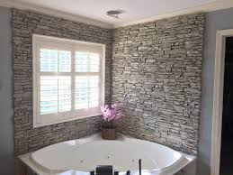 luxury corner bathtub with a backsplash surround with the look of real stacked stone