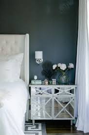 black and white bedroom with mirrored nightstand and gray greek key rug