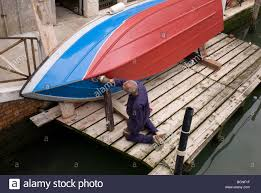 man painting boat hull