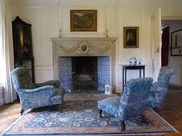 william morris s country house in the cotswolds turlish tiles around the fireplace and blue chairs