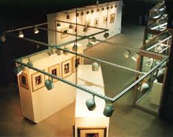 gallery track lighting. view from overwalk showing 4 display cubes south wall and glass cases gallery track lighting