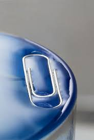 a paper clip on water which appears blue here due to the colour of the