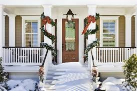 inviting front doorway with snow on porch stairs and garlands on columns
