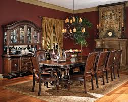 extra long varnished wooden table with bench and numerous upholstered dining chairs