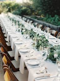 Flat ropes of greenery, small white flowers, candles, glass elements, and  longest