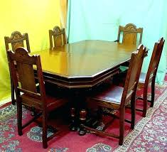 this handsome dark oak dining room set consists of a table that has fold away leaf and 6 chairs one which is captains chair with square w