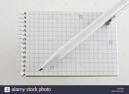 An Open Spiral Bound Notebook With Grid Paper And A White Pen Stock