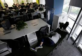 bed in office. Kou Meng, Product Manager Of RenRen Credit Management Co., Sleeps On A Camp  Bed At The Office Early Morning, In Beijing, China, April 27, 2016.