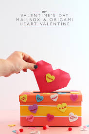 hand putting a pink origami heart into a colorful valentine s day mailbox covered in conversation heart