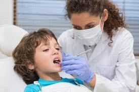 Pediatric Dental Hygienist Pediatric Dentist Examining A Little Boys Teeth In The Dentists 360535