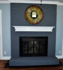 painted brick fireplace with blue paint color brick stone fireplace having glass cover with black frame and white wooden storage
