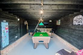 the converted garage has a pool table darts board and television while the walls