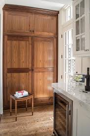 white kitchen with stained oak pantry cabinets