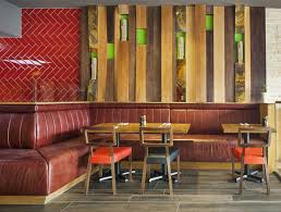 ceilings inspired by temples and colourful lighting fixtures complete the geometric look alongside a lime green wall overlaid with blocks of wood