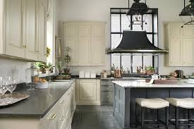 spacious cream and blue kitchen is fitted with cream cabinets donning brass pulls and a black quartz countertop holding a sink with a polished nickel