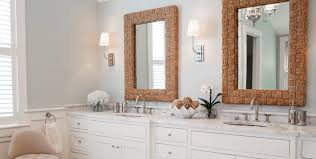 the white cabinets give this room a really clean look and feel the decorative square mirrors are the perfect choice as an accent in this bathroom