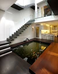 Modern Indoor Koi Pond Of Contemporary Home With Stained Timber Deck And  Floating Staircase Also Glass