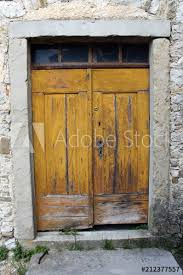 old yellow wooden doors with small glass top windows and heavy stone frame put in traditional stone wall