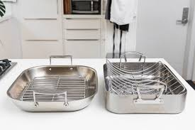 the multiclad pro and all clad flared roasting pans sitting side by side on a
