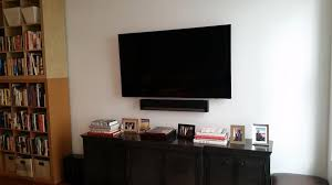 flat screen tv on wall with surround sound. to provide a surround sound experience, istallers used sonos system. this allows speakers located in various locations of the room receive flat screen tv on wall with