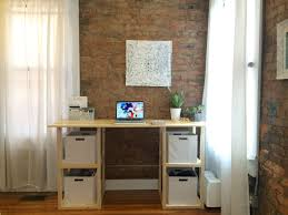 a diy desk by a brick wall and windows