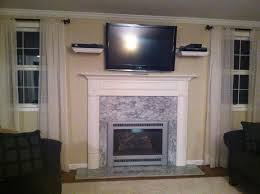 wall mounted tv with shelving above fireplace