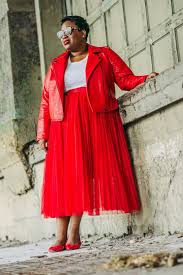a red leather jacket a red pleated midi skirt a white tee red