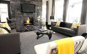 view in gallery black and white interior with yellow accents and tv mounted above the fireplace