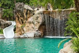 A large pool complex with high artificial stone walls and a water slide  that snakes down