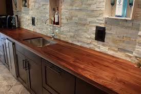 walnut countertop with undermount sink and stone back splash