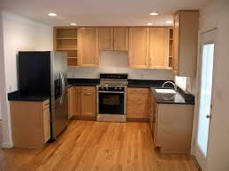 small kitchen design with wooden kitchen cabinets white painted walls wooden floor and black marble kitchen