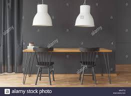 Schwarze Stühle An Den Hölzernen Tisch Unter Weißen Lampe In