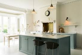 l shaped kitchen with dark cupboars and light flooring by magnet