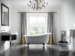 interesting bathroom with vintage style white slipper clawfoot bathtub and pedestal sink plus chandelier lighting decor