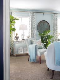 simplel small living room light blue armchairs vintage patterned chusion patterned curtains window big plant