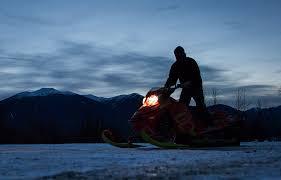 clint pelletier of edmonton alta is silhouetted while loading his snowmobile onto