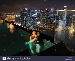 infinity pool singapore night. 24-02-2017 Marina Bay Sands Singapore - Young Couple In The Infinity Pool Of Hotel Singapore. Is Famous For Its View Over Night R