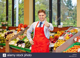 Smiling Store Manager In A Supermarket Holding His Thumbs Up Stock