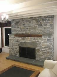 faux stone wall fireplace panels for living room with white wood ceiling beams pendant lamp and laminate hardwood floor tiles plus fireplace with black